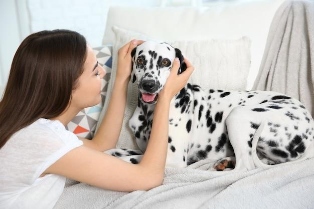 Właścicielka z dalmatyńczykiem siedzi na kanapie