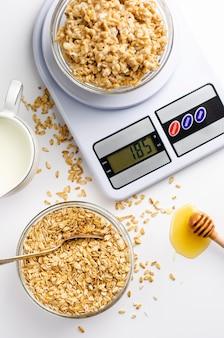 Właściwe menu żywieniowe na śniadanie z płatkami owsianymi na cyfrowej wadze kuchennej, mleku i miodzie