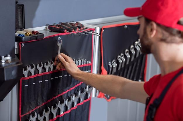 Właściwy wybór. mężczyzna w stojącej odzieży roboczej wybierając klucz z zestawu wiszącego na ścianie w warsztacie