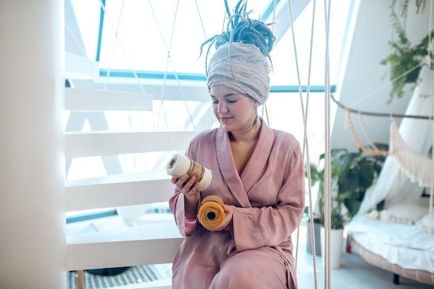 Właściwy wybór. młoda kobieta z fryzurą i bandażem na włosach w różowej szacie bada dwa motki nici w rękach do tkania