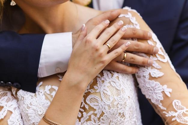 Właśnie małżeństwo. ręka w rękę nowożeńcy z obrączkami ślubnymi i bukietem ślubnym.