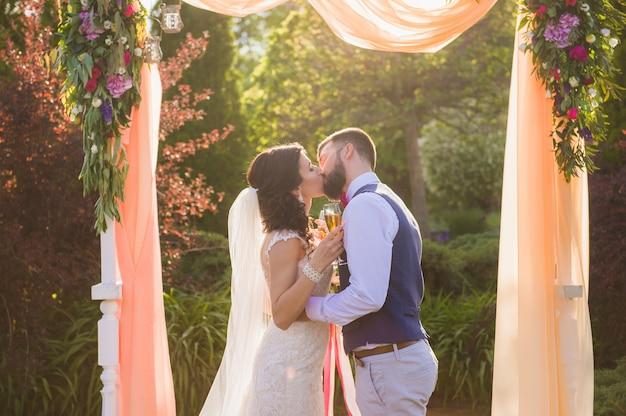 Właśnie zakochana para małżeńska pod łukiem na zewnątrz