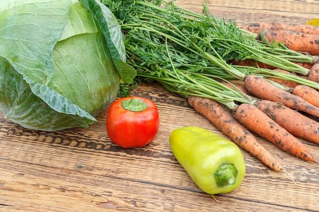 Właśnie zerwałem marchewki, kapustę, paprykę na drewnianych deskach. właśnie zebrałem świeże warzywa. dojrzałe warzywa po wykopaniu w ogrodzie. jedzenie organiczne.