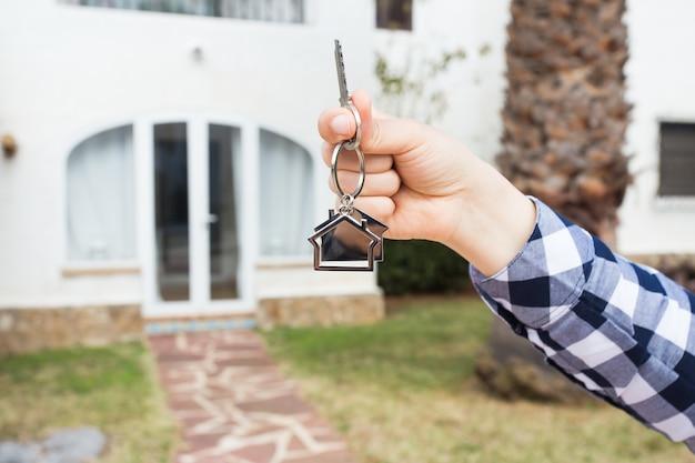 Własność i klucz koncepcji najemcy w kobiecej dłoni dla nowego domu i nieruchomości