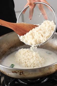 Wlej lepki ryż na patelnię, zbliżenie łopatki na patelnię z lepkim ryżem gotującym się na kuchence. przetwarzanie szefa kuchni przygotowującego lepką przekąskę ryżową (lemper) w kuchni