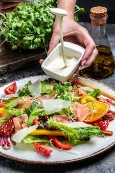 Wlej topiony ser na wierzch sałatki z kawałkami wędzonego łososia, sałatą, suszonymi pomidorami i ziołami, koncepcja zdrowego odżywiania, smaczny obiad,