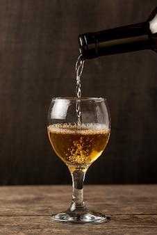 Wlewając białe wino do kieliszka