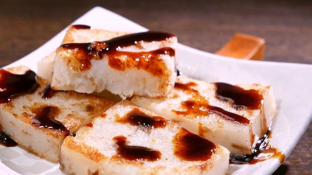 Wlewając czarny sos sojowy na gotowe do spożycia pyszne ciasto z rzepy, chińskie tradycyjne lokalne danie rzodkiewka w restauracji, z bliska, skopiuj miejsce.