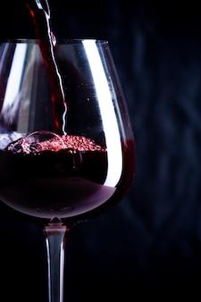 Wlewając czerwone wino do szklanki