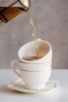 Wlewając herbatę do filiżanki