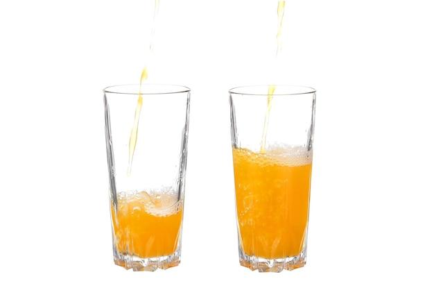 Wlewając sok pomarańczowy do szklanki na białym tle