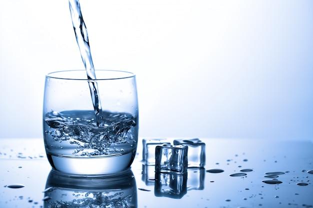 Wlewając wodę do szklanki w pobliżu kostek lodu z rozpryskami