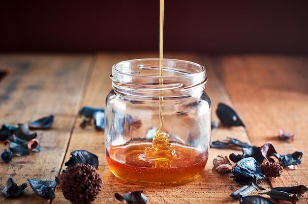 Wlewając złoty miód do szklanego słoika na drewnianym stole