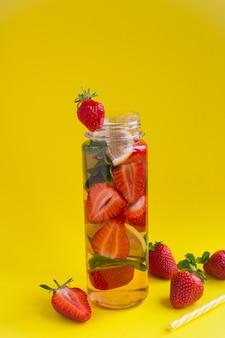Wlewana lub oczyszczająca wodę z truskawkami i cytryną w butelce na żółtym tle. miejsce na kopię. zbliżenie.