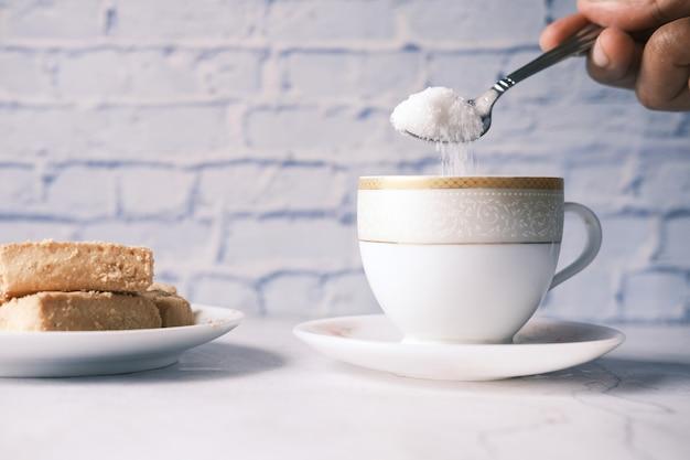 Wlewanie białego cukru do filiżanki herbaty