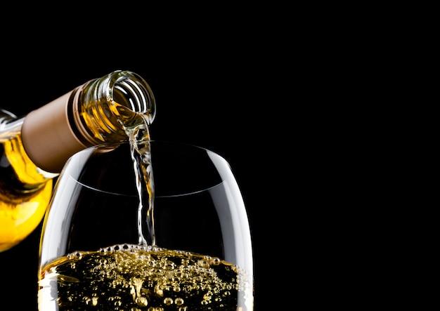 Wlewanie białego wina z butelki do szklanki na białym tle