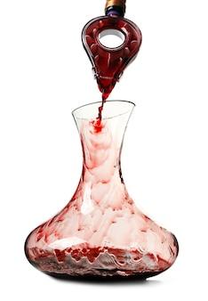 Wlewanie czerwonego wina do karafki na białym tle