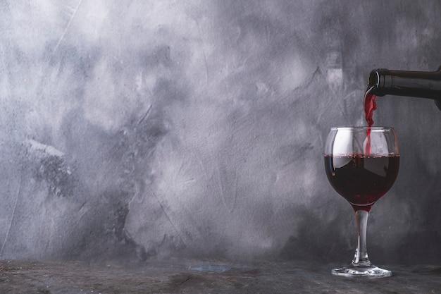 Wlewanie czerwonego wina do kieliszka na szarej ścianie. copyspace
