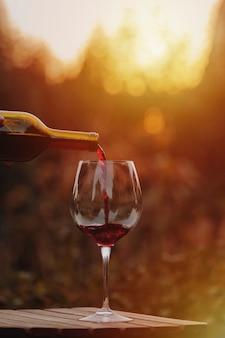 Wlewanie czerwonego wina do kieliszka.