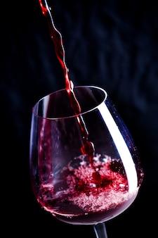 Wlewanie czerwonego wina do kieliszka