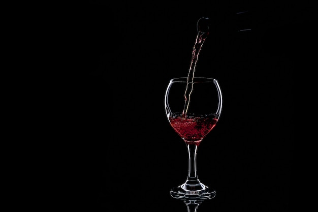 Wlewanie czerwonego wina do szklanki na ciemno. na białym tle sylwetka