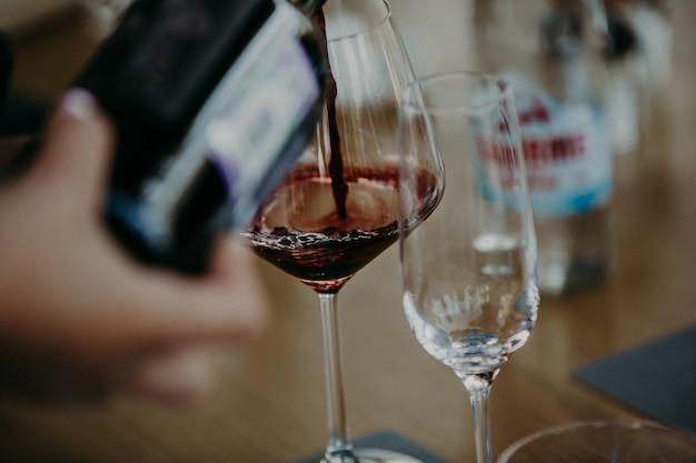 Wlewanie czerwonego wina z butelki do kieliszka