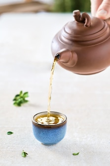 Wlewanie gorącej japońskiej zielonej herbaty do filiżanki (miski) w stylu orientalnym na jasnym stole. selektywne skupienie się na filiżance. zbliżenie, pomysł na herbatę, minimalizm