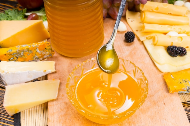 Wlewanie miodu do miski na półmisku serów z dużym asortymentem różnych serów z boku do wykorzystania jako zdrowy dip