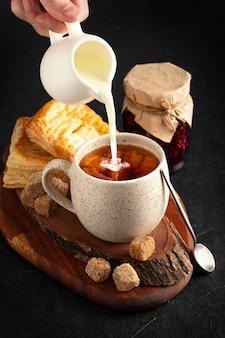 Wlewanie mleka do kubka gorącej herbaty