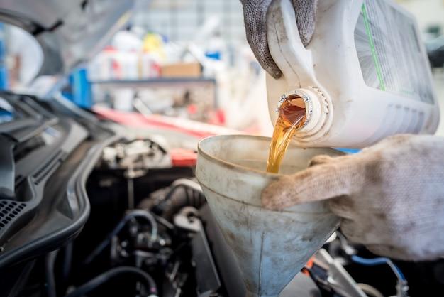 Wlewanie oleju silnikowego do maszynowni., złoty olej podczas wymiany oleju samochodowego w warsztacie lub centrum serwisowym., wnętrze centrum pielęgnacji samochodów