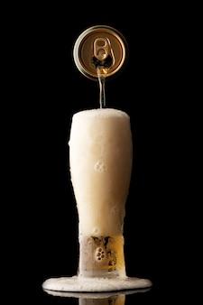 Wlewanie piwa do szkła na czarnym tle