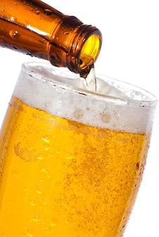 Wlewanie piwa do szklanki na białym tle