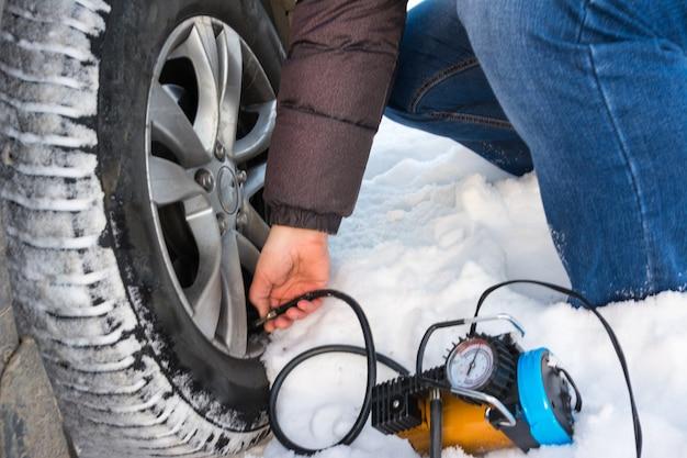 Wlewanie powietrza do opony samochodowej. zima. zbliżenie naprawy przebitej opony dmuchawy kompresora.
