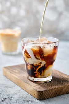 Wlewanie śmietanki w mrożonej kawie w szkle typu rocks