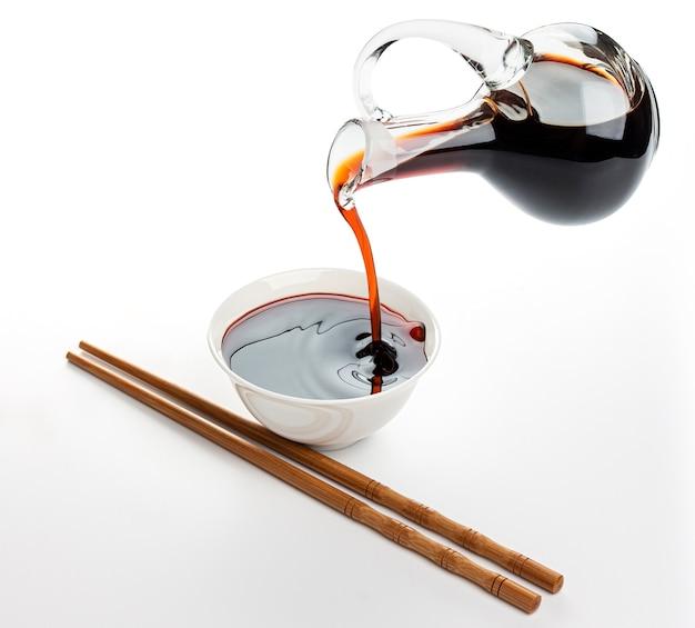 Wlewanie sosu sojowego i bambusowe pałeczki na białym tle
