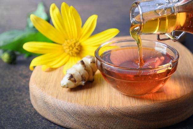 Wlewanie syropu z karczocha jerozolimskiego do miski z kwiatami i korzeniem