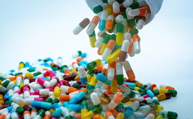 Wlewanie wielokolorowych kapsułek z plastikowej butelki z lekiem. koncepcja nadużywania antybiotyków.