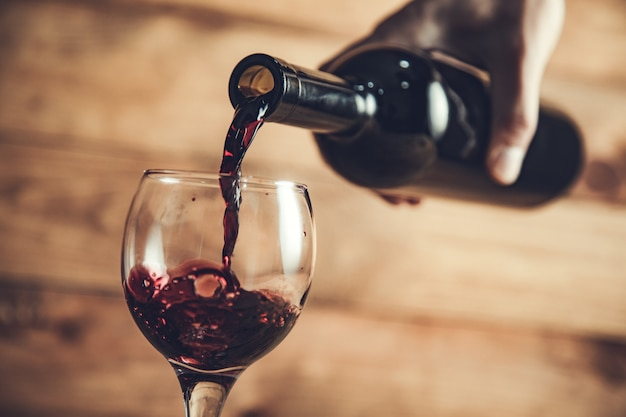 Wlewanie wina gronowego do kieliszka na stole