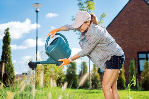 Wlewanie wody. blondynka w czapce z daszkiem, wylewająca wodę ze zraszacza ogrodowego na rośliny na zewnątrz