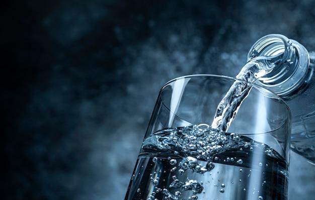 Wlewanie wody z butelki do szklanego om czarnego teksturowanego tła z miejscem na kopię