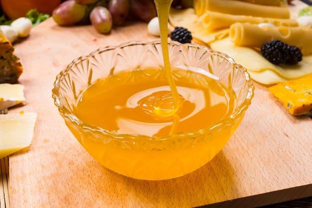 Wlewanie zdrowego złocistego miodu do okrągłej szklanej miski na stole do stosowania jako dip i pasta do smarowania