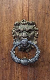 Włochy. antyczna kołatka na stare drewniane drzwi.