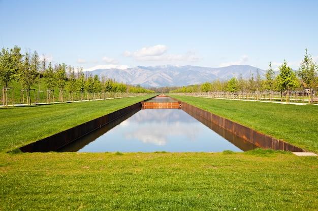 Włochy - basen z wodą w zielonym polu z górami alp w tle