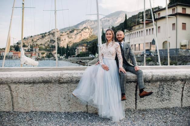 Włochy, jezioro garda. piękna para nad brzegiem jeziora garda we włoszech u podnóża alp. mężczyzna i kobieta siedzą na molo we włoszech.