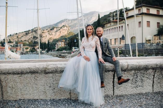 Włochy, jezioro garda. piękna para nad brzegiem jeziora garda we włoszech u podnóża alp, mężczyzna i kobieta siedzą na molo we włoszech.