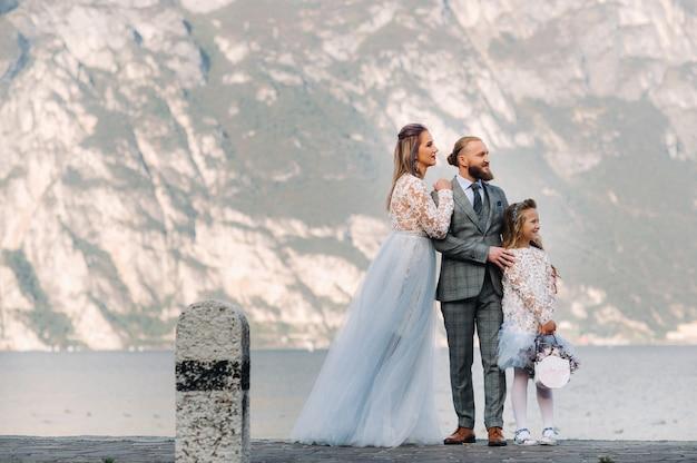 Włochy, jezioro garda. piękna rodzina nad brzegiem jeziora garda we włoszech u podnóża alp. ojciec, matka i córka we włoszech.