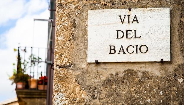 Włochy - miasto pienza. znak ulicy via del bacio (ulica kiss)