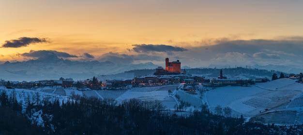 Włochy piemont: winnice niepowtarzalny krajobraz zimowy zachód słońca, średniowieczny zamek serralunga d'alba na szczycie wzgórza, tło ośnieżonych szczytów alp, panoramiczny widok na dziedzictwo włoch