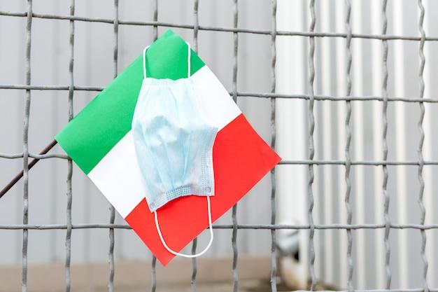 Włochy poddają kwarantannie, powstrzymają koronawirusa. coronavirus rozprzestrzenia się we włoszech. nowy koronawirus w europie ue. włoska flaga i medyczna maska ochronna na klatce. zatrzymaj epidemię wirusów.