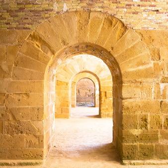 Włochy - stary zamek syracuse na sycylii. łuki wykonane z kamienia w perspektywie.